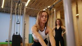 做在健身房的年轻女人健身 做力量锻炼的妇女 观看她的另一名妇女 股票视频