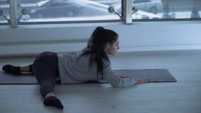 做在健身房的年轻灵活的美女锻炼 舒展一个年轻女运动员 股票录像