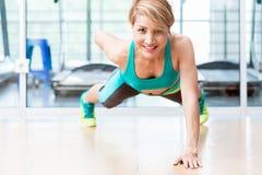 做在健身房的微笑的少妇一胳膊pushup 库存照片