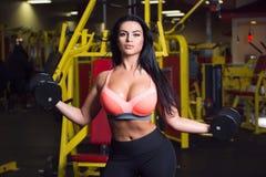 做在健身房的性感的健身妇女体育锻炼与哑铃 免版税库存照片