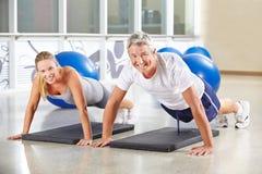 做在健身房的男人和妇女俯卧撑 免版税库存照片