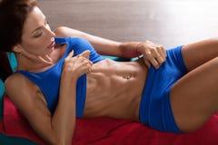 做在健身房的肌肉妇女吸收咬嚼 免版税库存照片