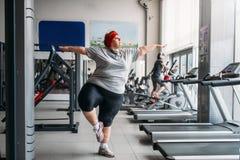 做在健身房的肥胖妇女平衡锻炼 免版税库存照片