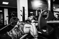 做在健身房的英俊的年轻人卧推锻炼 库存照片