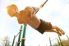 做在健身房的英俊的肌肉爱好健美者人锻炼 库存照片
