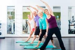 做在健身房的资深和青年人体操 免版税图库摄影