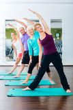 做在健身房的资深和青年人体操 库存图片