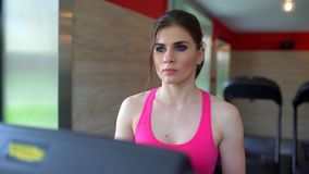 做在健身房的运动可爱的白种人少妇心脏锻炼 健身女孩,在跑桃红色的上面的sportwoman  影视素材