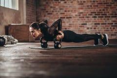 做在健身房的适合的女性强烈的核心锻炼 免版税库存照片