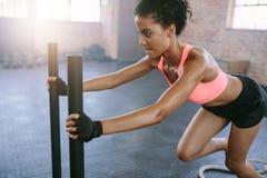 做在健身房的非洲妇女强烈的锻炼 库存图片