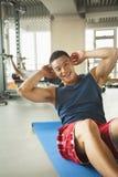 做在健身房的年轻人仰卧起坐 库存照片