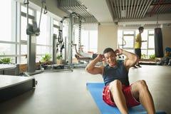 做在健身房的年轻人仰卧起坐 库存图片