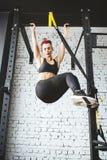 做在健身房的年轻健身妇女引体向上 免版税库存照片