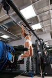 做在健身房的年轻性感的健身教练员引体向上 免版税库存照片