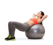 做在健身球的十几岁的女孩锻炼 图库摄影