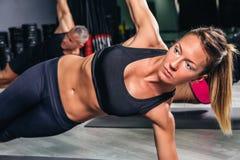 做在健身类的白肤金发的妇女锻炼 库存图片