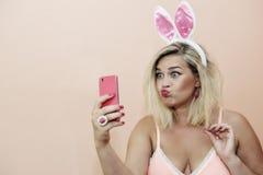 做在兔子的妇女性感的样式selfie鞠躬耳朵和桃红色女睡袍-智能手机摄影 免版税库存照片