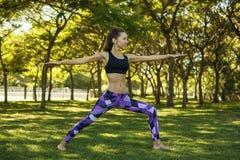 做在公园战士姿势的美丽的女孩瑜伽 免版税图库摄影