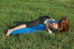 做在公园的少妇瑜伽锻炼 库存图片