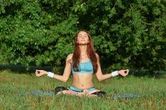 做在公园的少妇瑜伽锻炼 免版税库存图片