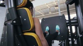 做在力量训练用具的亚裔妇女锻炼在健身房 HD从右到左射击与滑子(移动式摄影车) 股票视频