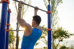 做在单杠的肌肉人引体向上,训练室外公园健身房的大力士早晨 免版税库存照片