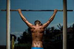 做在单杠的运动员引体向上 库存照片