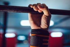 做在单杠的运动员锻炼 免版税库存图片