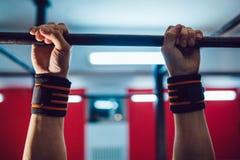 做在单杠的运动员锻炼 库存图片