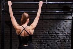 做在单杠的年轻肌肉妇女背面图照片锻炼对砖墙在十字架适合的健身房 免版税库存图片