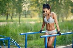 做在双杠晴朗室外的美丽的健身妇女锻炼 免版税图库摄影
