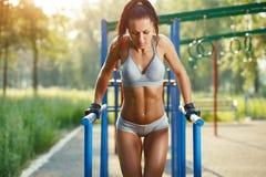 做在双杠晴朗室外的美丽的健身妇女锻炼 库存照片
