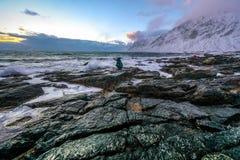 做在古老石头的旅行摄影师图片在冷的挪威海岸在晚上时间 海岛lofoten Beautif 免版税库存照片