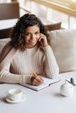 做在咖啡馆的快乐的非裔美国人的妇女笔记 库存图片