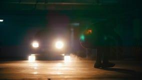 做在地下停车处,慢动作的一年轻人freerunner的剪影杂技跃迁 股票视频