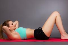 做在地板上的美丽的年轻健身妇女锻炼 库存图片