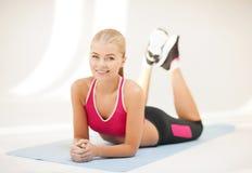 做在地板上的运动的妇女锻炼 免版税库存照片