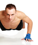做在地板上的年轻健身人俯卧撑 库存照片