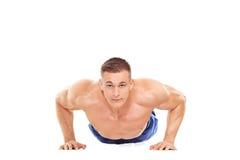 做在地面上的男性运动员俯卧撑 库存照片