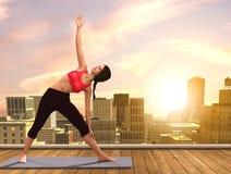 做在城市屋顶的瑜伽妇女姿势 皇族释放例证