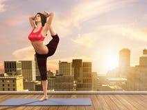 做在城市屋顶的瑜伽妇女姿势 库存图片