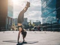 做在城市街道上的年轻运动妇女手倒立在现代摩天大楼中 锻炼 平衡的,瑜伽锻炼 免版税库存照片