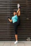 做在城市街道上的运动灵活的少妇站立的分裂锻炼 免版税库存照片