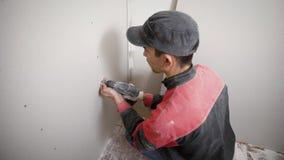 做在墙壁的被集中的工作者孔有运转的钻子的在站点 股票录像