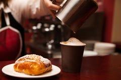 做在外带的杯子咖啡和甜禁令的女服务员 免版税图库摄影