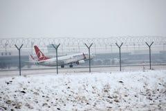 做在多雪的机场的土耳其航空喷气机出租汽车 免版税库存图片
