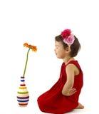 做在大丁草花前面的红色礼服的小女孩一个愿望被隔绝 免版税库存图片