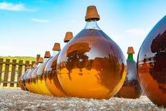做在大回合玻璃古色古香的篮装的细类颈大坛瓶的自然甜点心麝香葡萄利口酒白酒外部在弗龙蒂尼昂,南部 图库摄影