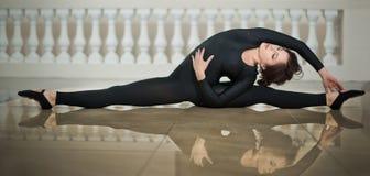 做在大理石地板上的优美的芭蕾舞女演员分裂 执行在光滑的地板上的华美的跳芭蕾舞者分裂 免版税库存照片