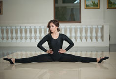 做在大理石地板上的优美的芭蕾舞女演员分裂 执行在光滑的地板上的华美的跳芭蕾舞者分裂 免版税图库摄影